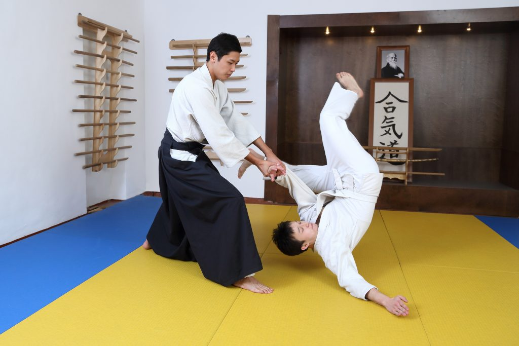Two aikido practitioners demonstrating a common move in a traditional aikido dojo