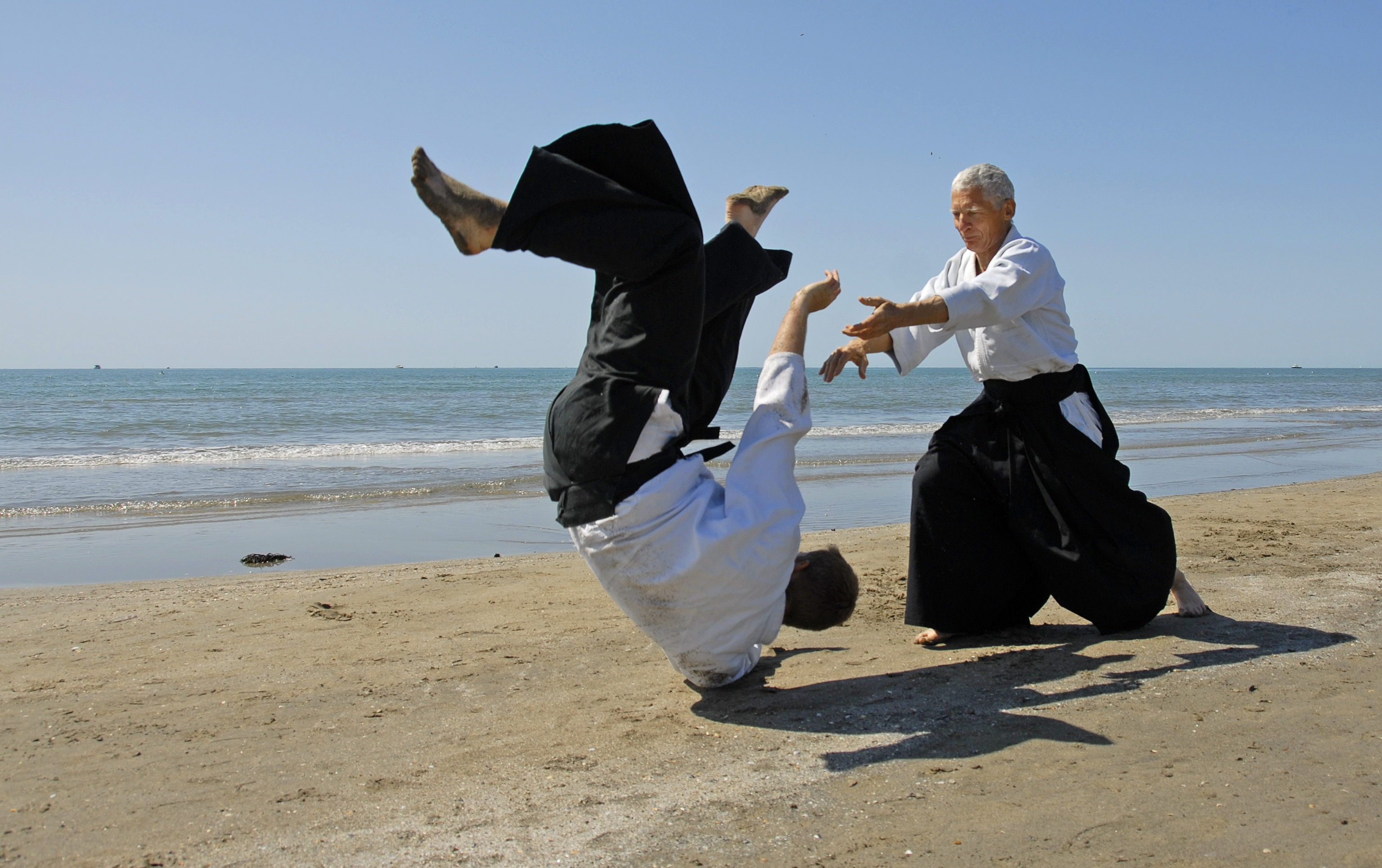 two adult men practicing aikido on the coast of a body of water